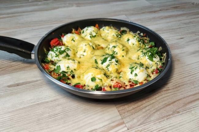 Вареные яйца с овощами и сыром на сковороде